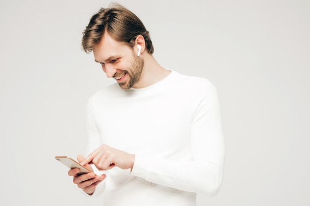 Handsome smiling hipster lumbersexual businessman model wearing white casual sweater and trousers. fashion stylish man posing against gray