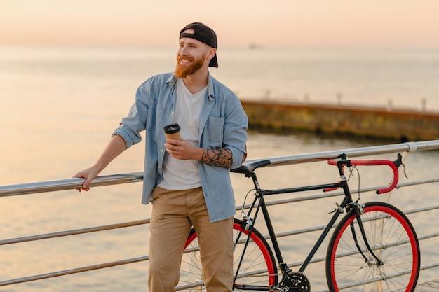 Красивый улыбающийся рыжий бородатый мужчина в стиле хипстера в джинсовой рубашке и кепке с велосипедом на утреннем восходе солнца у моря, пьющий кофе, путешественник, ведущий здоровый активный образ жизни
