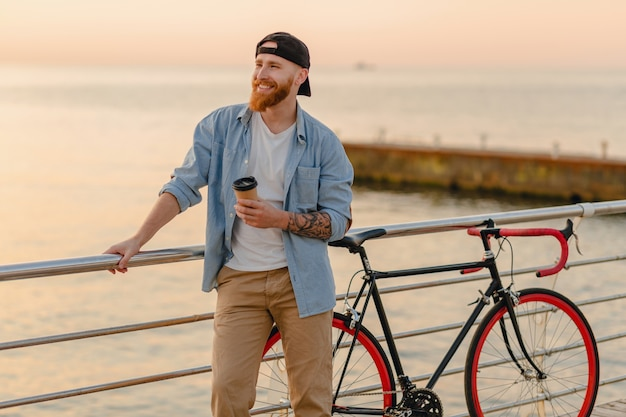 Handsome smiling hipster style ginger bearded man wearing denim shirt and cap with bicycle in morning sunrise by the sea drinking coffee, healthy active lifestyle traveler
