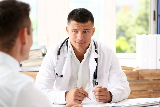 Handsome smiling male doctor hold silver pen
