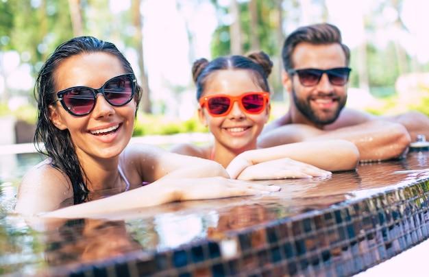 ハンサムな笑顔の男と彼らと一緒にかわいい興奮した女性は、ホテルで休んでいる間、夏のプールで楽しんでいます。