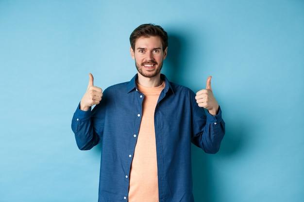 Красивый улыбающийся человек, поддерживающий, показывая большие пальцы в одобрении, хвалит хорошую работу, стоя счастливым на синем фоне.