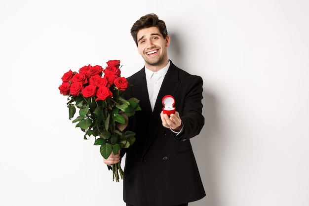 Handsome smiling man in black suit, holding roses and engagement ring, making a proposal to marry him, standing against white background