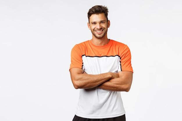 ハンサムな笑みを浮かべて男ボディービルダー、胸の上の腕を組んで、スポーツtシャツを着用します。