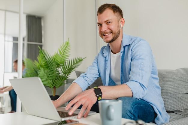 Красивый улыбающийся мужчина в рубашке расслабленно сидит на диване у себя дома за столом, работая онлайн на ноутбуке из дома