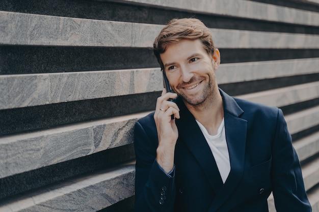 대화를 즐기는 밖에서 스마트폰으로 세련되게 말하는 잘생긴 웃는 남자