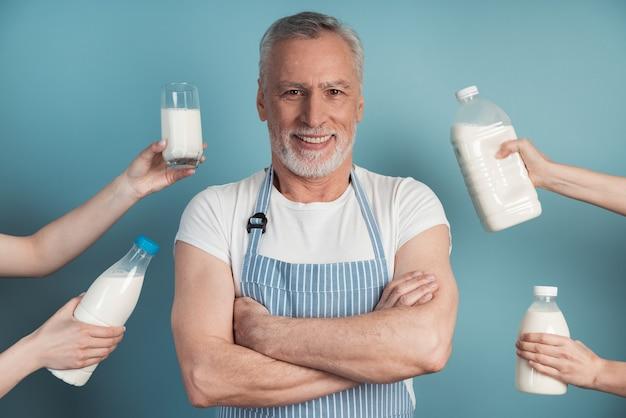 잘 생기고 웃는 남자가 파란색 벽에 서서 사람들의 손에 우유를 들고 마치 그에게 제안하는 것처럼