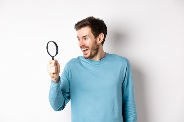 Handsome smiling man looking through magnifying glass with amazed face, found interesting promotion, standing on white background