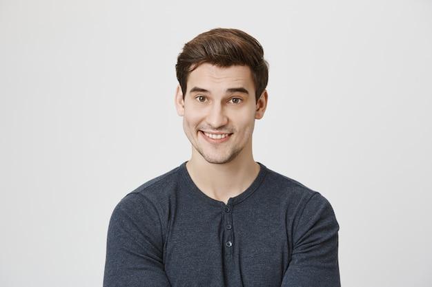 Uomo sorridente bello che osserva con incredulità