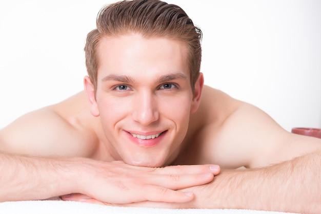 스파 살롱에서 마사지 책상에 누워 잘 생긴 웃는 남자와 긴장. 미용 치료 개념.