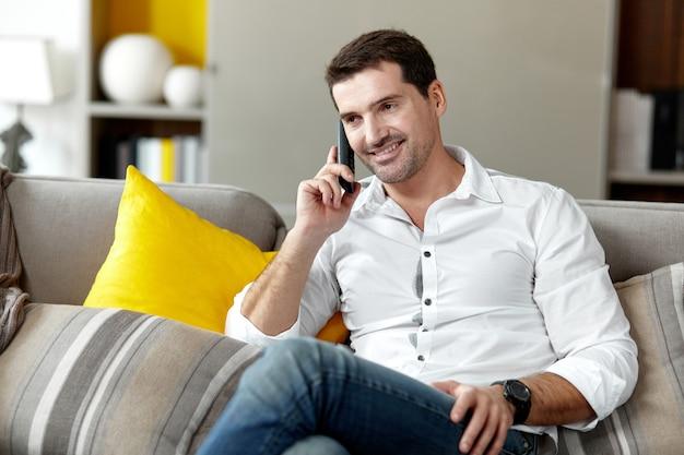 Красивый улыбающийся человек звонит по телефону, сидя на диване в своей гостиной. горизонтальный вид.