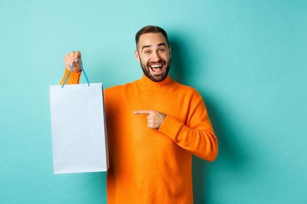 Красивый улыбающийся человек указывая пальцем на хозяйственную сумку, покупая в магазинах, довольный на синем фоне.