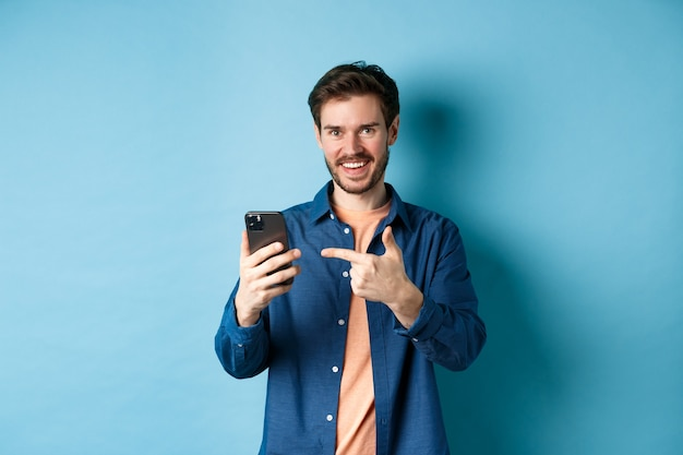 잘 생긴 웃는 남자 스마트 폰에서 손가락을 가리키고 파란색 배경에 서있는 응용 프로그램을 추천, 카메라에 기쁘게보고.