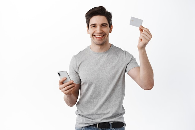 Handsome smiling man showing plastic credit card and using smartphone to pay online, shopping in app, standing satisfied against white wall