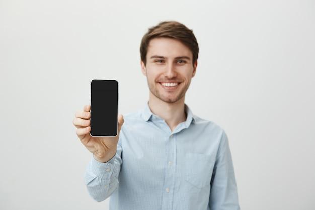 スマートフォンの画面を示すハンサムな笑みを浮かべて男