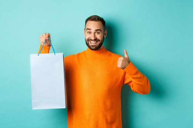 Handsome smiling man showing thumbs-up and shopping bag, recommending store,s tanding against turquoise wall