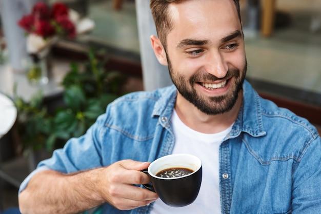 屋外のカフェのテーブルに座って、コーヒーを飲むハンサムな笑顔の男