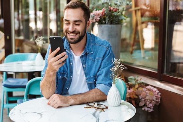 Красивый улыбающийся человек, сидящий за столиком в кафе на открытом воздухе, используя мобильный телефон