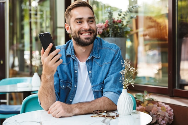 Handsome smiling man sitting at the cafe table outdoors, using mobile phone