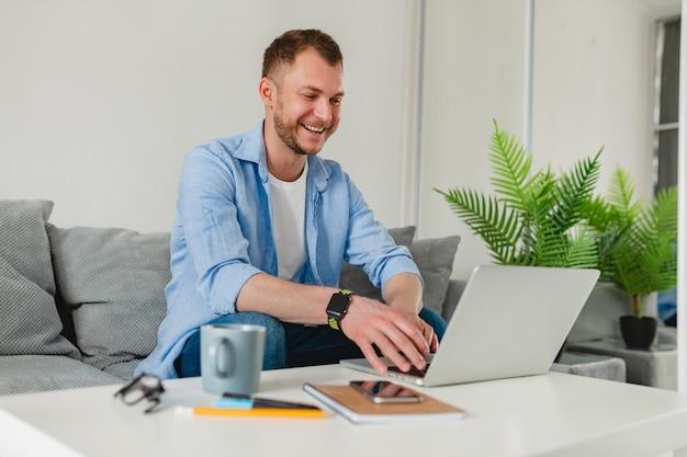 Красивый улыбающийся человек сидит на диване и пьет чай дома за столом, работая онлайн на ноутбуке из дома