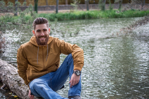 강에 떠있는 나무의 줄기에 앉아 잘 생긴 웃는 남자. copyspace 오른쪽.
