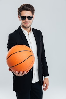Handsome smiling man in sunglasses and black suit showing basket ball over grey wall