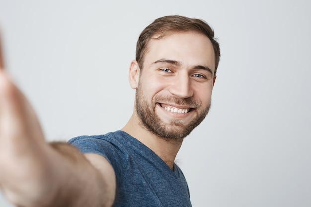 Красивый улыбающийся человек, принимая селфи