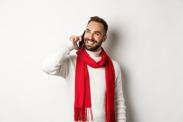 잘생긴 웃는 남자 전화 통화, 만족 찾고, 겨울 스카프와 스웨터, 흰색 배경에 서 있는