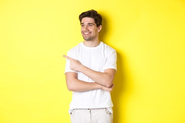 Handsome smiling man in white clothes, looking and pointing finger left at banner, standing over yellow background.
