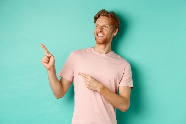 ミントの背景の上にtシャツで立って、左上隅のバナーを指して、喜んで見える赤い髪とひげを持つハンサムな笑顔の男。