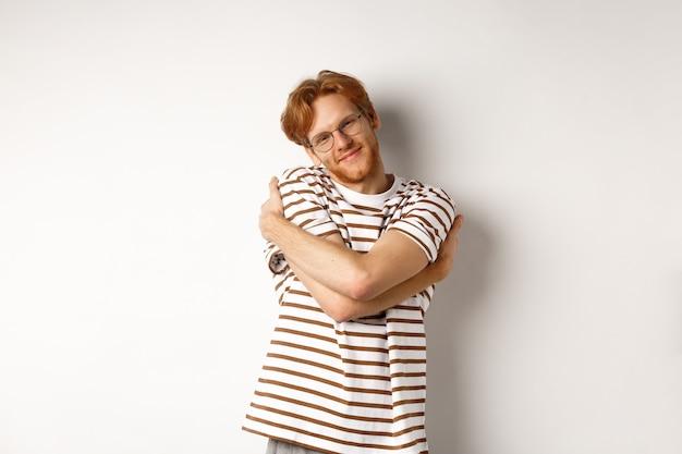 빨간 머리와 수염을 편안 하 게 찾고, 자신을 포옹 하 고 카메라 행복 한 얼굴, 흰색 배경보고 잘 생긴 웃는 남자.
