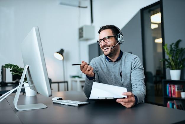 Красивый усмехаясь человек работая на справочном бюро.