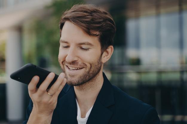 Красивый улыбающийся аккуратный бородатый офисный работник разговаривает по громкой связи, стоя на улице