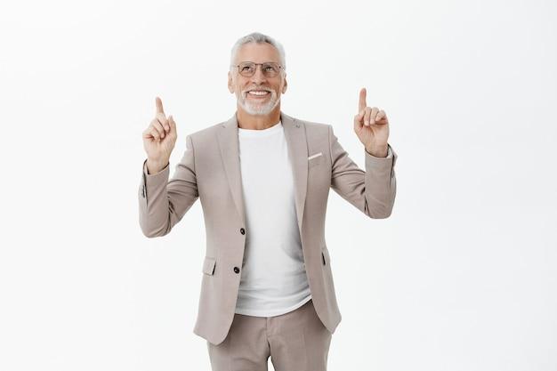 Bello sorridente vecchio uomo d'affari in tuta che punta e che osserva in su