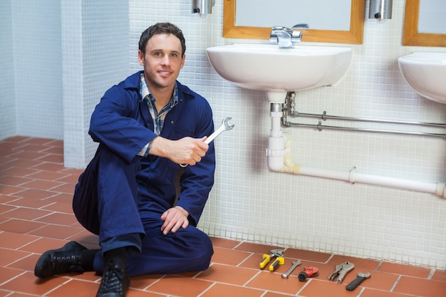 Handsome smiling plumber sitting next to sink holding wrench in public bathroom