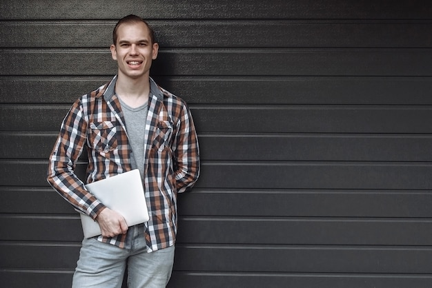 Handsome smiling portrait of a happy guy standing against a gray wall with a laptop in his hand