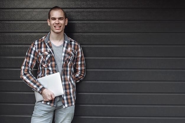 그의 손에 노트북과 회색 벽에 서 행복 한 남자의 잘 생긴 웃는 초상화