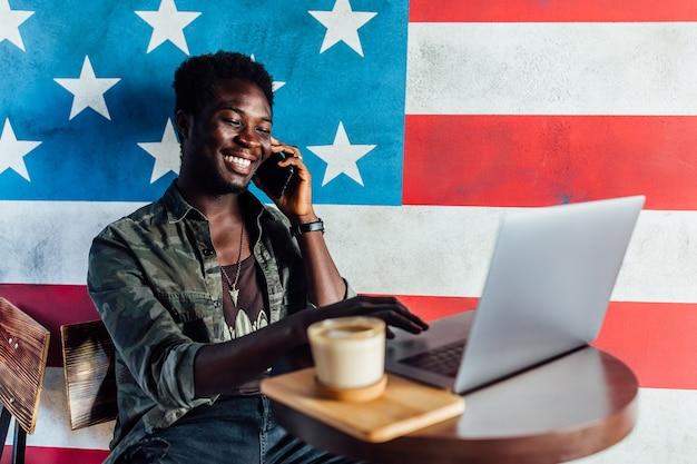 Красивый улыбающийся успешный афро-американский мужчина в строгом костюме, используя портативный компьютер для удаленной работы и улыбается.