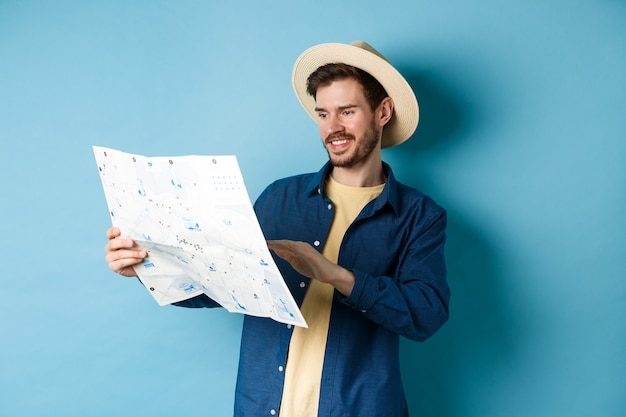 Handsome smiling tourist in straw hat looking at map, choosing travel road, planning a vacation, standing on blue background.
