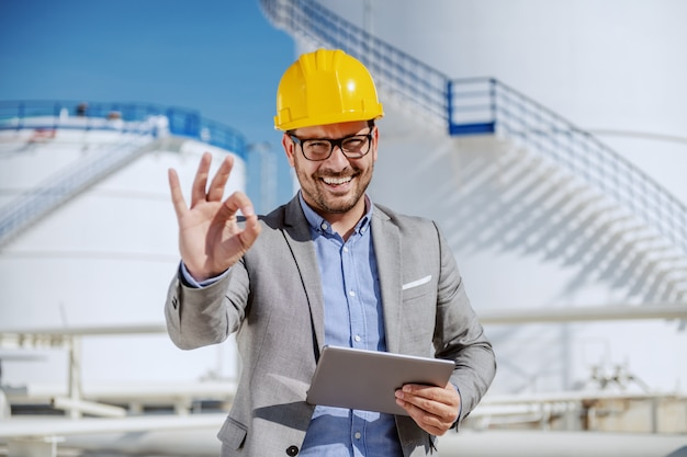 Handsome smiling unshaven businessman in suit and with helmet on head holding tablet and showing okay sign.