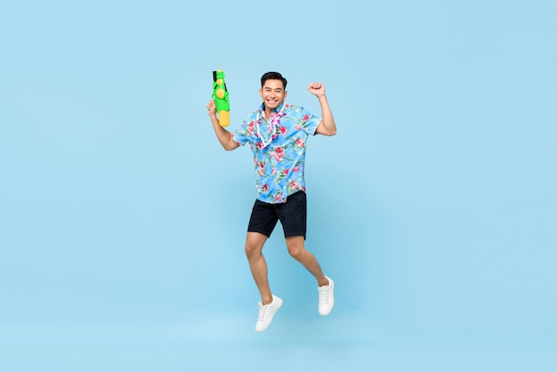 Handsome smiling young asian man playing with water gun and jumping for songkran festival in thailand and southeast asia
