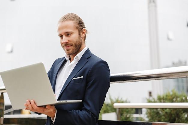 Красивый улыбающийся молодой бородатый бизнесмен, стоящий на открытом воздухе на улице, работая на портативном компьютере