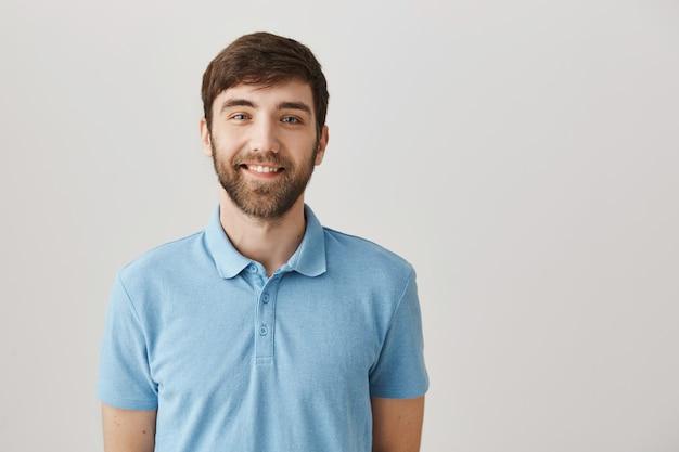 Bello sorridente giovane uomo barbuto in posa