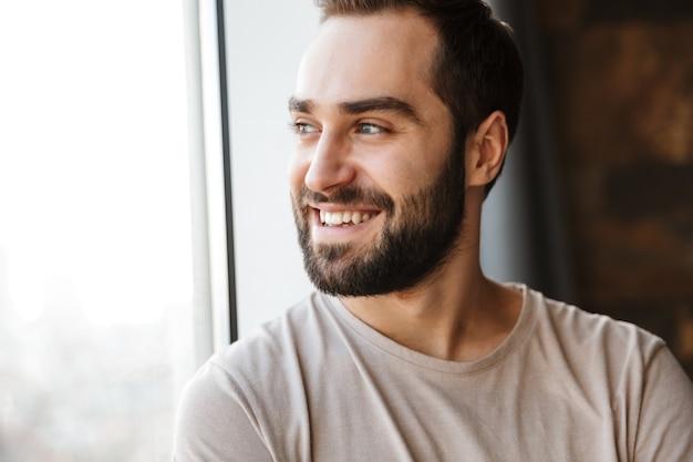 家の窓に立って、目をそらしてハンサムな笑顔の若いひげを生やした男