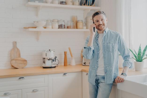 수염을 기른 잘생긴 청년은 집에서 원격으로 온라인 작업을 하는 동안 부엌에서 휴대전화로 통화하는 캐주얼 옷을 입고 고객과 계약 서명에 대해 성공적인 대화를 나눴습니다.