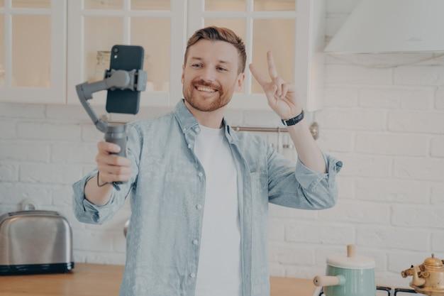 수염으로 셀카를 찍거나 짐벌 안정 장치를 사용하여 스마트폰으로 스트리밍하고 집에서 부엌 배경에서 평화 신호를 보내는 잘생긴 젊은 브루네트 남자는 평상복을 입는다