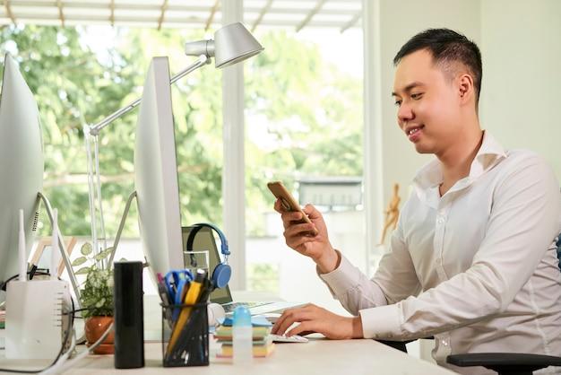 オフィスのテーブルに座って、彼のスマートフォンでテキストメッセージに答えるハンサムな笑顔の青年実業家