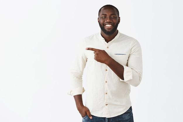 Bel ragazzo giovane sorridente in posa contro il muro bianco