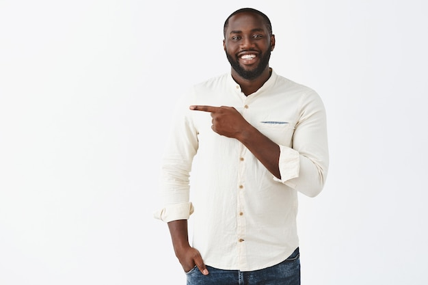 Handsome smiling young guy posing against the white wall