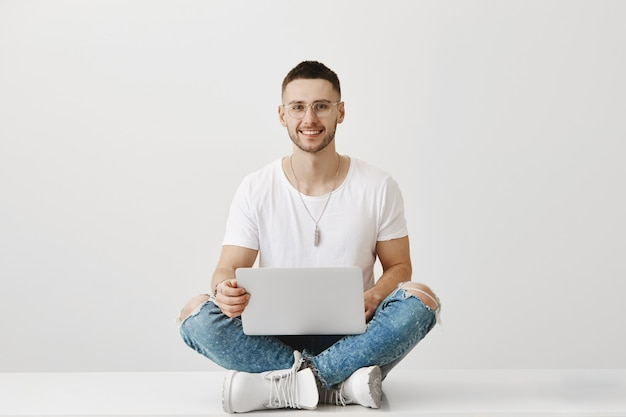 Handsome smiling young guy with glasses posing with his laptop